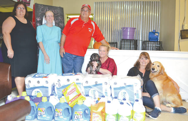 From left, Angelika Paxman, treasurer of the Champaign County Farmers Market, Michelle Comer, secretary of the CCFM, and Jeff Conley, president of the CCFM, present a donation of $150 worth of cleaning supplies to Kelly Hamilton and Becki Brown, co-founders of the Save A Shelter Shih Tzu dog rescue mission, on Tuesday.