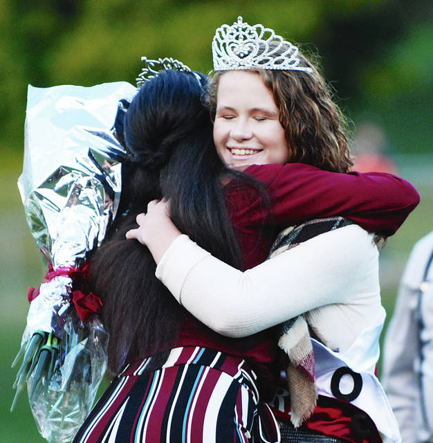 Urbana High School 2018 Homecoming Queen Marissa Horn (right) closes her eyes as she embraces 2017 Homecoming Queen Taje Mack during the crowning ceremony during football pregame on Friday evening. The Hillclimbers hosted Shawnee.