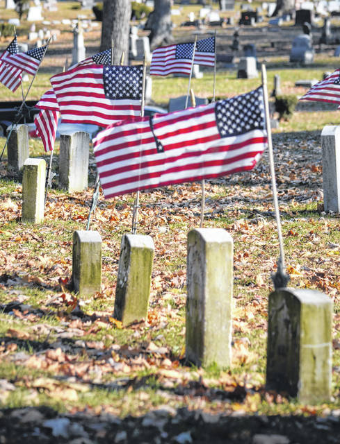 """A small contingent of local veterans and residents braved the cold and gathered at Soldiers Mound in Urbana's Oak Dale Cemetery Sunday morning for a short Veterans Day service. American Legion Post 120 provided a 21-gun salute and bugler Warren Haney, who played """"Taps."""""""