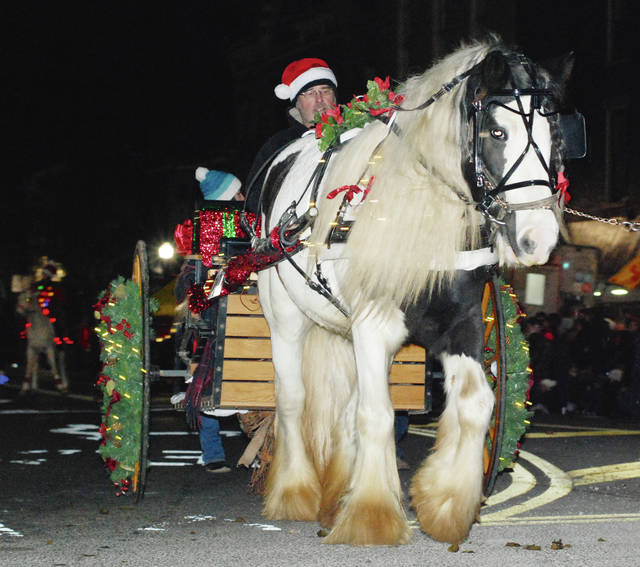 Horse-drawn wagons and carriages, like the one pictured above, brought Christmas to downtown Urbana in traditional style Friday night.