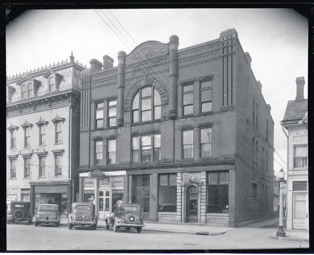 Then – This is a circa 1937 photo (CCHS #0134) of the north side of the 100 block of Scioto Street in Urbana. Moore's Business College was at 100 Scioto St. In the next building was Parllete Electric Company at 104 Scioto St., then Miami Granite Co. at 106 Scioto St. and Dr. Poffenberger, Dentist, at 106 1/2 Scioto St. Note the decorative street lamp at the corner of the alley entrance.