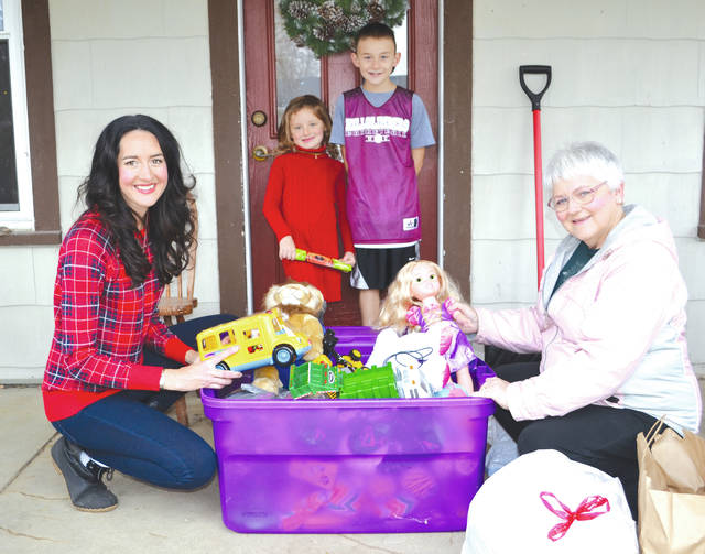 Toy Swap organizer Julie Yohey, left, and her children Vyla, 6, and Dexyn, 8, help frequent donor Jodi Kitchen unload a bucket of toys at their house for the event at Life-net Church on Dec. 4.