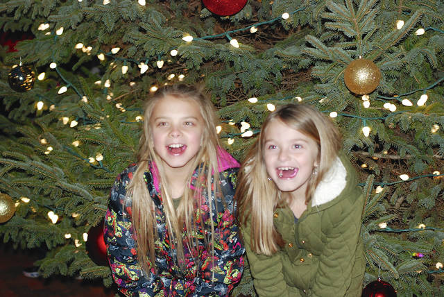 Nine-year-old Clohee Jordan (left) and her sister Carlee Wooten (age 7 1/2) pose for a portrait in front of the newly-illuminated Christmas tree in downtown Urbana's Monument Square District on Friday evening. A holiday horse parade and the first appearance of Santa Claus at Oxner's General Store rounded out the festivities. See more photos in Monday's edition of the Urbana Daily Citizen.