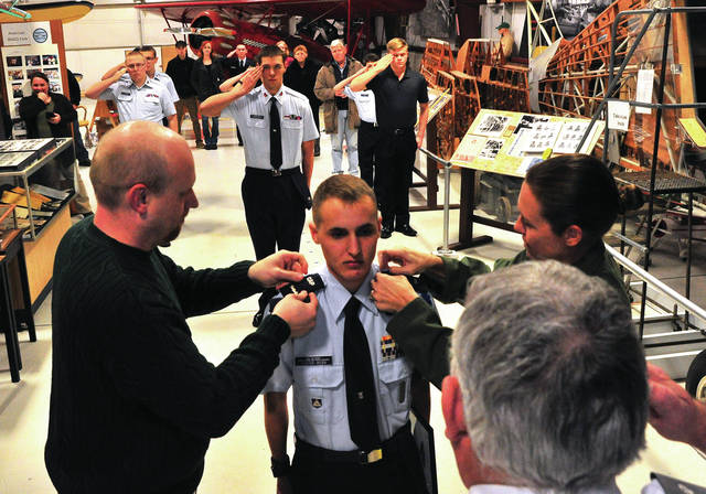 Mike Ullery | Troy Daily News Newly promoted Civil Air Patrol Cadet Captain Max Foster-Webb is pinned with his new insignia by his dad, Paul Webb, and Lt. Col Monyca Uecker, USAF, during ceremonies at the WACO Museum and Aviation Learning Center last week. Foster-Webb, 17, from Springfield, was awarded the Civil Air Patrol's Amelia Earhart Award in addition to the promotion.