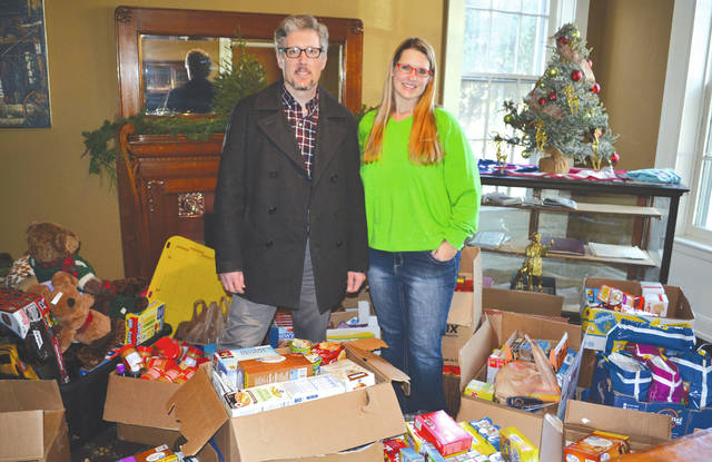 "Champaign County Chamber of Commerce board members Ty Henderson and Stacey Logwood stand amid piles of ""kid-friendly"" food donated to the Chamber's effort for local school backpack programs. The programs help students in need by giving them essentials to take home over the holiday vacation. Monday's sorting process at the Chamber and subsequent distribution of items through the Caring Kitchen capped off a Christmas collection effort coordinated by the Chamber."