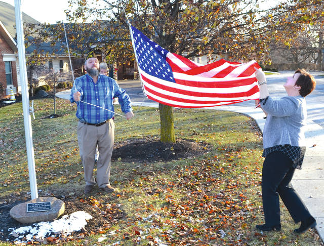 Scotty Lykins, an Air Force veteran with VFW/DAV, and Celeste Artis, an Army veteran currently working as assistant manager at Hearth and Home in Urbana, perform a flag raising ceremony outside the retirement community on Tuesday after their old flag had become deteriorated.