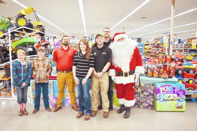 Siblings Tyler, left of Santa, and Monica Slaven, center, of DeGraff accept over 200 gifts from the Lima Big R Store for their toy drive.