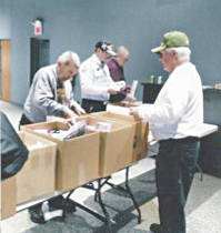 Gene Baker, Jerry Henderson, Jim Barnhart and Gary Bennett sort and pack care packages at the VFW/DAV building.