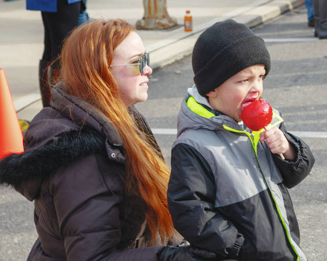 Heather and Hunter Stritenberger enjoy the Christmas in the Village Parade while Hunter eats a candy apple on Saturday in Mechanicsburg. Santa arrived in the village to collect the wish lists of Mechanicsburg children.