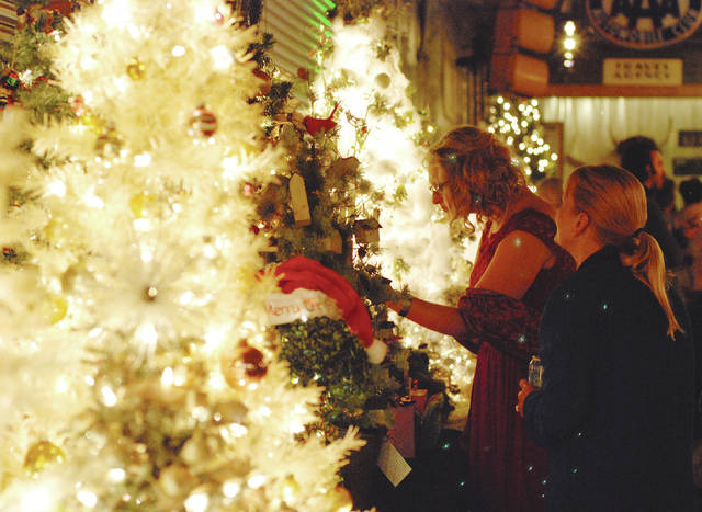 Browsers inspect each uniquely decorated tree as the row of offerings creates a warm glow prior to Wednesday night's auction.