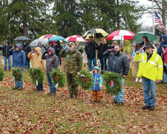 "Urbana Mayor Bill Bean, right, leads a group of volunteers and local dignitaries at the ""Wreaths Across America"" dedication in Oak Dale Cemetery on Dec. 15."