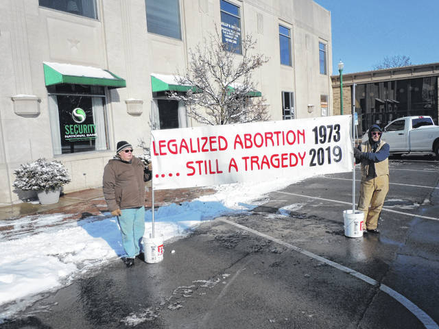 Allan Baker, left, and Terry Spridgeon hold a pro-life banner during the Jan. 20 Witness event on Monument Square.