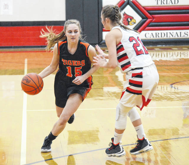 West Liberty-Salem's Grace Estes (15) drives around Triad's Kristin Bailey (21) on Thursday.