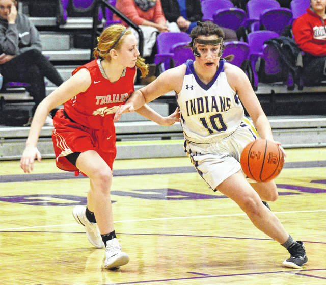 Mechanicsburg's Lani Wilhelm (10), sporting a new mask to protect her recently-broken nose, turns the corner on a dribble drive Thursday night against Southeastern.