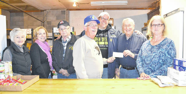 Lions Club president and Mechanicsburg Mayor Greg Kimball (center, front) donates $1,440 raised from the Lions Club Christmas raffle to the village's Food Pantry, which he estimates will buy 6,000 pounds of food from Second Harvest Foodbank in Springfield. Food Pantry volunteers are in the rear row from left to right: Sheila Scheiderer, Amy Boeck, Loren Scheiderer, Scott Spinner, Bill Miller and Carrie Eleyet.