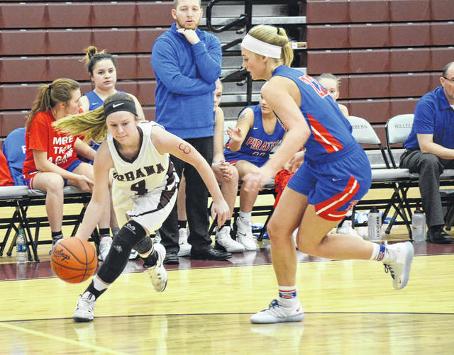 Urbana's Makenna Radford (4) goes around Riverside's Shelby Giles on the baseline during Monday's game at UHS.