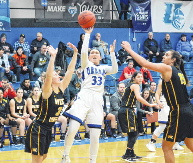 Urbana University's Megan Beachy (33) shoots a fade-away jumper between a pair of defenders on Wednesday versus West Liberty.