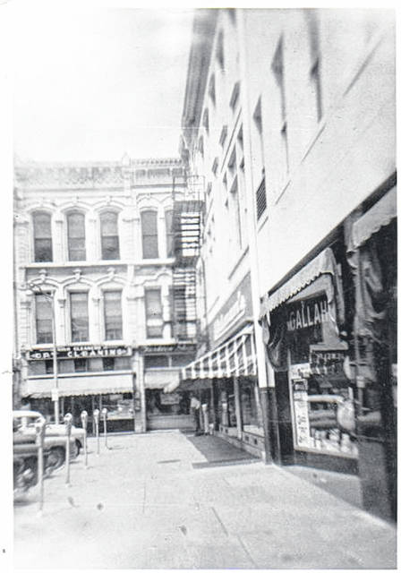 "Then - This a 1957 photo (#A2803) of the northwest corner of Monument Square, Urbana. On the corner at North Main Street is Gallagher Drug Store. Next to it is Uhlman's Department Store and in the corner is Nigh's Dry Cleaners. Currently at these locations are Massage on Monument Square, Sellman Insurance Group and Jeff Graves Insurance in the corner. Note the parking meters, sometimes ""affectionately"" referred to as ""one-armed bandits."" The Champaign County Historical Society thanks Mildred Frazier for sharing this photo."