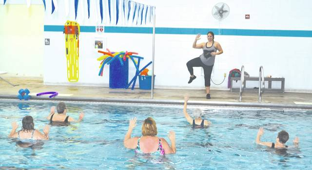 YMCA Health Enhancement Director Jennifer Post leads an aquatic aerobics class at the Champaign Family YMCA on Wednesday.