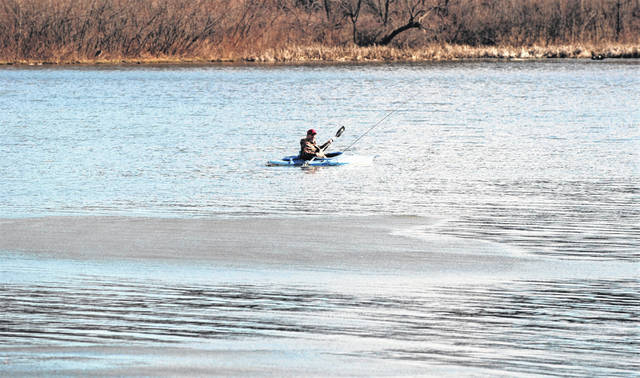 An unidentified fisherman in a kayak navigates the water at Kiser Lake on Tuesday. Temperatures peaked at 57 degrees with bright sunshine and few clouds, but strong winds foretold of the cold air about to enter the area.