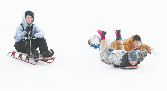 Bradley Mefford (left), Oliver Grim and Jayden Gibson went sledding down the hill in front of Urbana High School on Tuesday as cleanup continued after Winter Storm Harper - which closed local schools. By Wednesday afternoon, warmer temperatures and rain were already eating away at the weekend's heavy snowfall. Sledding at UHS is a winter tradition.