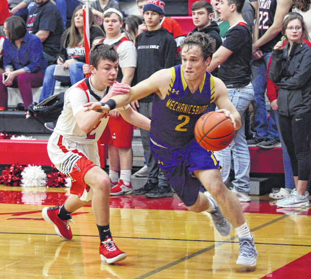 Mechanicsburg's Joey Mascadri (2) goes around Triad's Drew Campbell on the baseline Tuesday at Triad.