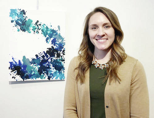 Michele Stokes stands with her artwork in the Champaign County Arts Council's gallery.