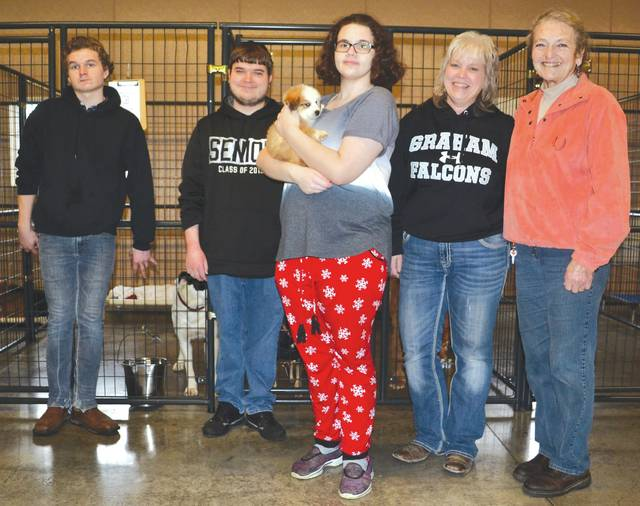 From left, Graham High School junior Wyatt Drown, senior Shane Meyer, senior Lauryn Tully, Transition Coordinator Mindy Lensman and kennel Manager Jeretta Aldridge stand in front of the kennels that they assembled on Jan. 5.