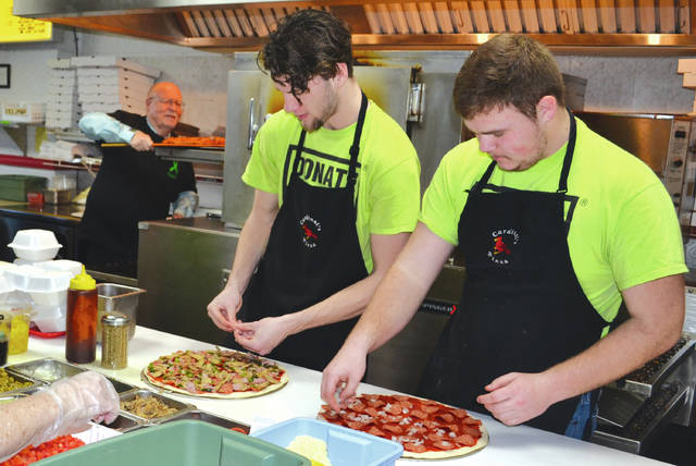 Cardinal's Pizza owner Don VanZant (left) pulls a pizza from the oven during the restaurant's 6th annual pizza sampler fundraiser for the Drew Mason Memorial Scholarship on Monday, during which he also celebrated his 70th birthday. Employees Cam Atchison (center) and Hunter Talbot (right) remain hard at work preparing pizzas for the oven.