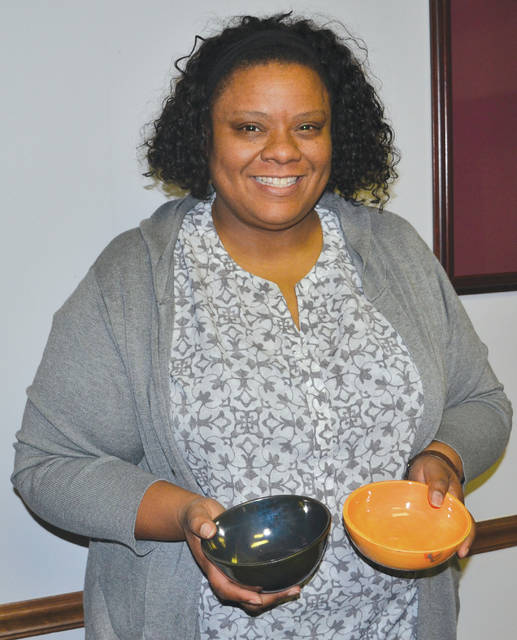 Tyra Jackson, executive director of Second Harvest Food Bank, holds two of the ceramic bowls that may be used to serve soup at the Feb. 28 Empty Bowls fundraiser.