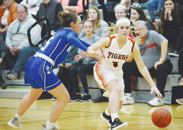 West Liberty-Salem's Kelsey Day (3) dribbles around Miami East's Morgan Haney (5) on Monday during the Division III sectional final at Covington. Day, absent the first time the two teams met in December, scored a game-high 22 points to power the Tigers to victory.