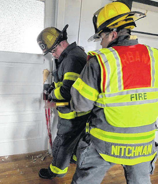 Firefighters Tyler Wolf and Adam Nitchman practice making a forcible entry inside the former Local Intermediate school on Wednesday.