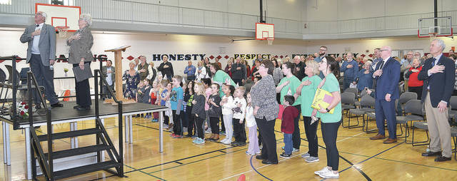 Than Johnson and Mary Lee Gecowets (at left on platform) recite the Pledge of Allegiance along with Champaign Family YMCA preschoolers and nearly 200 attendees of the 20th anniversary celebration on Wednesday in the YMCA gymnasium.