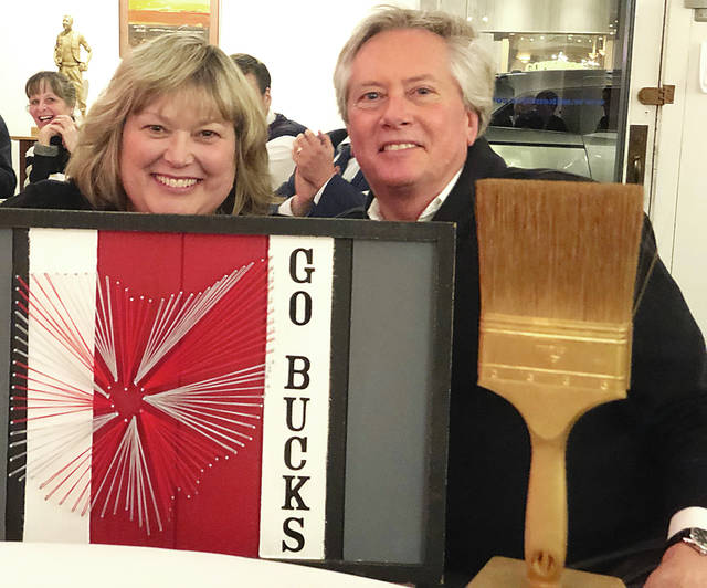 "The annual ""Bad Art by Good People"" fundraiser dinner and auction was held Friday evening at the Champaign County Arts Council on Miami Street. Brian Nicol (right) is shown with his Ohio State themed string art piece, which won the voting online and in person. During Friday's dinner/auction, Nicol's wife Robbin (left) purchased the artwork. More than $13,000 was raised by the 2019 ""Bad Art by Good People"" event."