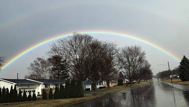 This photo of a rainbow hovering over wet Urbana pavement was emailed to the <em>Daily Citizen</em> by Urbana resident Larry Lokai between 6:16 and 8 p.m. Thursday. After this week&#8217;s spring-like weather, cooler weather has returned, but since March roared in like a lion, many hope it will depart like a lamb. The rainbow coincidentally heralded the opening of St. Patrick&#8217;s Day weekend.