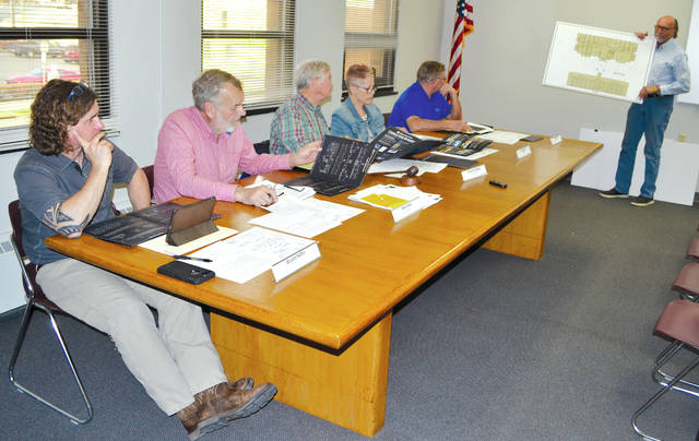Urbana Hotel investment group co-chair Mike Major (far right) holds up plans for the new hotel as he requests a variance from the Board of Zoning Appeals (from left to right): Bryant Heflin, Marty Hess, Chairman Vince Gonzalez, Lisa Haulman and Charlie Zerkle.