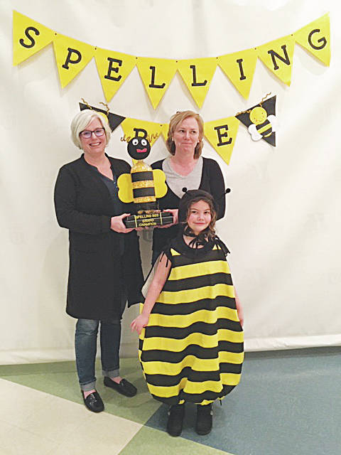 "Emily Rozmus (left) and Amy Boeck of Our Saviour Church, Mechanicsburg, won the second annual adult spelling bee hosted by the Champaign County Children's Literacy Foundation. Pictured as the ""bee"" is Bailey Burden."