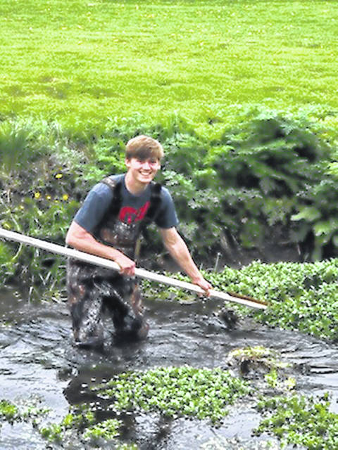 Kenny Hart cleans debris and overgrowth in Onion Creek at Lions Park in West Liberty.