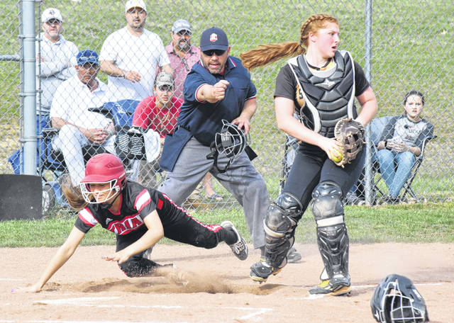 Triad's Sidney Louck (left) gets bumped off line by a collision at the plate with Shawnee catcher Alise Moneypenny on Thursday.