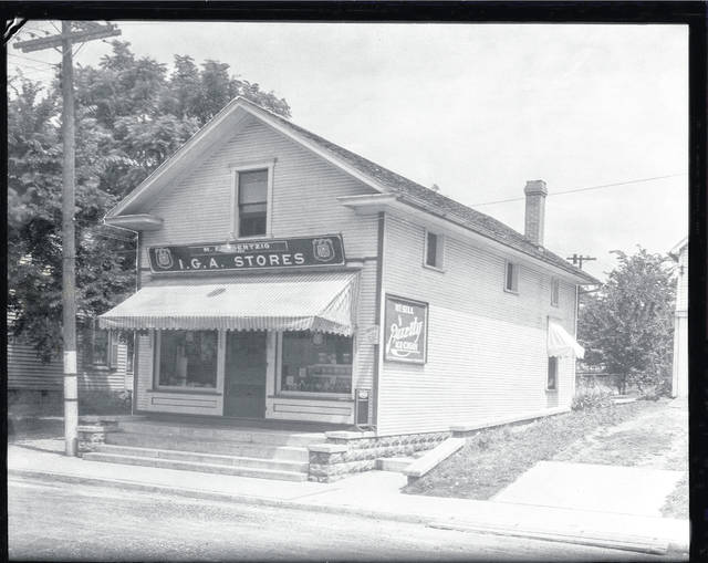 "Then – This is a circa 1920 photo (0404) of the M.E. Goertzig IGA grocery store located at 315 Sycamore St., Urbana. The sign on the south side of the building reads: ""We sell Purity Ice Cream"""
