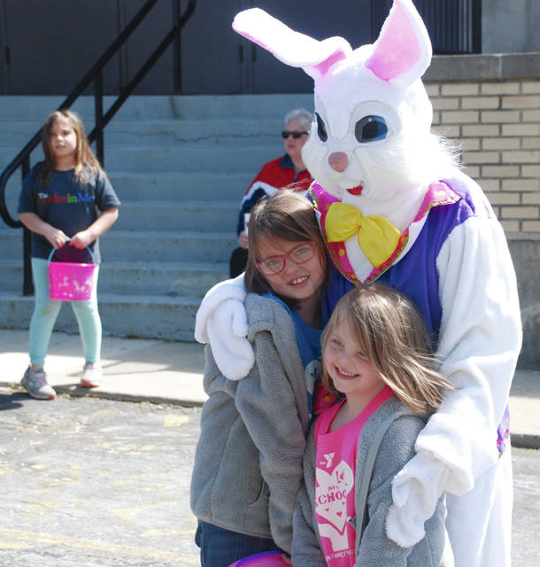 Ella Stambaugh (age 7) and Issie Woodruff (age 4) get a hug from the Easter Bunny on Saturday prior to the Easter Egg Hunt on the front lawn of Urbana High School on Saturday. Sponsored by the Fraternal Order of Police and Judge Gil Weithman and family, the egg hunt had been rescheduled from April 20 due to cold, rainy weather on Easter weekend.