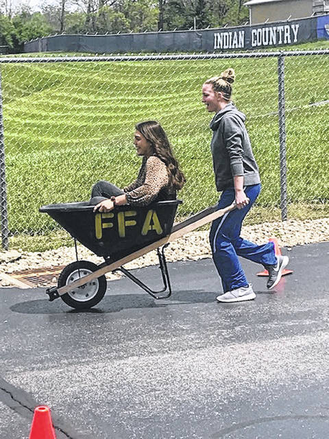 Burg FFA students Daytayviah Rodgers (in wheelbarrow) and Morgan Heizer compete in the wheelbarrow race as part of the Ag Olympics and FFA week.