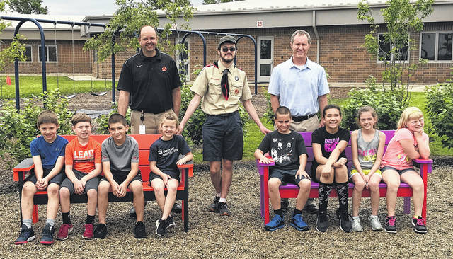 Students testing out the new benches are, from left, Miles Christison, Cohen Jenkins, Ivan Meister, Rachel Sanford, James Brehm, Nevaeh Gravely, Isla Leichty and Kathy Roehm. Standing behind them are, from left, Superintendent Kraig Hissong, Life Scout Matthew Schuster and Elementary Principal Aaron Hollar.