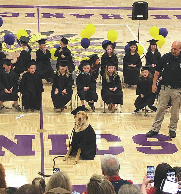 """Chief"" is given full graduation honors with the Mechanicsburg Elementary School kindergarten class on Thursday. Pictured at right is school resource officer Sgt. Chris Roberts."