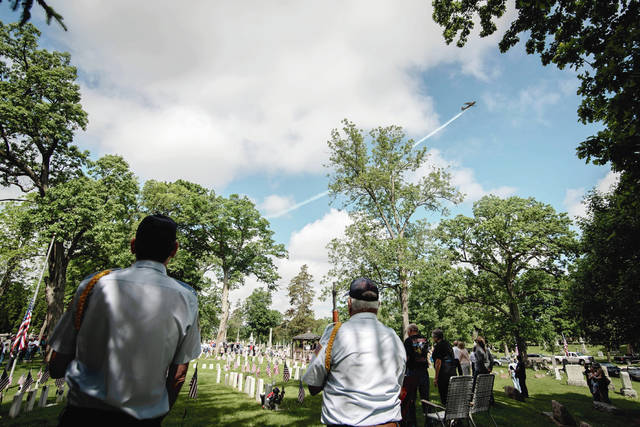 Local pilot Jim White provides a fly-over salute Monday morning during Urbana's Memorial Day observance in Oak Dale Cemetery.