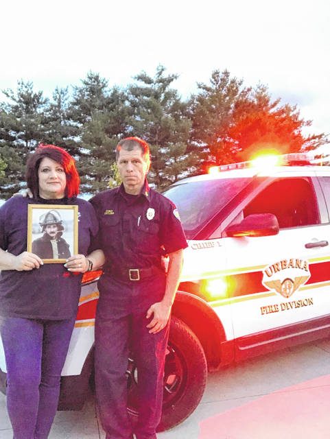 Urbana Fire Chief Dean Ortlieb and his wife, Karol, with a picture of her brother, Capt. Jeff Routte.