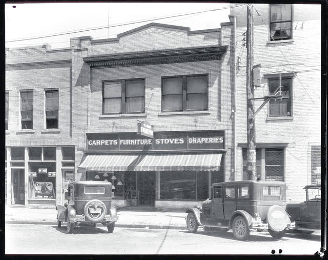 Then – This is a circa 1929 photo (0198) of the Strapp Furniture Store at 106 Miami St., Urbana. Carpet, stoves and draperies were also sold. Note that head-in parking was used then on Miami Street.