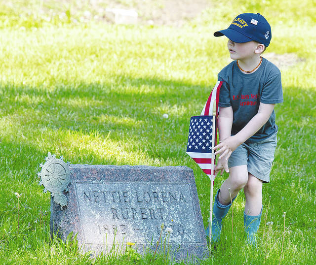 Vincent Deppen places a flag at Oak Dale Cemetery on Saturday as American Legion Post 120 members decorated military graves.