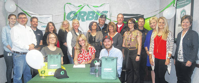 Caty Shoemaker, seated at center, signs her employment contract as an intern at ORBIS in Urbana. Seated at left is her manager, Laura Reed, materials manager, and seated at right is Shoemaker's fiancé, Sam McGill. Standing from left are Dan Szklany, ORBIS plant manager; Maegan O'Connor, human resources representative; Tom Walker, scheduler; Sharon Cook, buyer/planner; Shelley Fuller, plant scheduler; Julie McGill, Sam McGill's mother; Judy and Rodney McGill, McGill's aunt and uncle; Cindy and Perry Shoemaker, Shoemaker's parents; Jill O'Neal, Caty Shoemaker's sister; Dean Ortlieb, Urbana fire chief and a cousin of the Shoemaker family; Karen Chuvalas of Urbana University; Ashley Cook, business liaison of the Champaign Economic Partnership (CEP); and CEP Director Marcia Bailey.