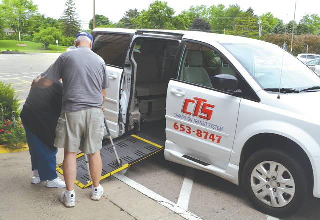 A Champaign Transit System driver known as JR assists Linda Parsons getting into a van at Kroger in Urbana on May 30.